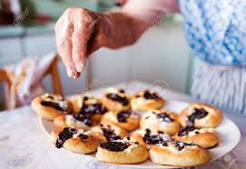 Senior Woman Baking Pies In Her Home Kitchen Sprinkling Freshly
