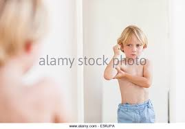 toddler looking in mirror. 5-year-old boy looking in a mirror. - stock image toddler mirror