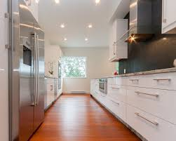 Galley Kitchen Design Features High End White Cabinet With Long Handles And  Black Backsplash