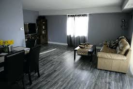 dark gray laminate flooring living room cream leather sofa black dining table grey wall painting wood