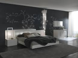 the crystal chandelier white bed and tables appear to float against the black accent wall