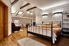 attic master bedroom. attic master bedroom features exposed beam ceiling with skylights brick wall black metal frame bed