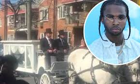 Two horses are pulling the carriage and hearse, decorated with white. Pop Smoke Fans Line The Streets To Bid Final Farewell To Slain Rapper During Funeral Procession Daily Mail Online