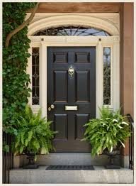cream colored trim helps soften the black door on this traditional home