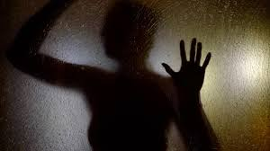 mystic female silhouette is holding hands on glass screen in dark studio stock footage