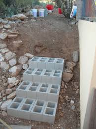 dirt rocks and cinder block steps and foundation concrete blocks retaining wall