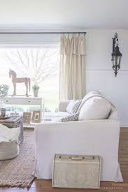 a cozy farmhouse living room with beautiful linen slipcovered sofas see how to get this