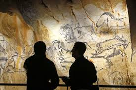 visitors look at the life size replica of grotte chauvet or chauvet cave in