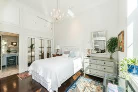 mirrored closet doors hardwooden floor chandelier lamp rectangular mirror accent rug glass table dresser nightstand wall
