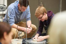 photo essay curiosity and wonder campus news uw la crosse uwl student max scheurell pictures left teaches a student to use a clay potters