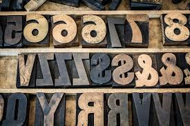 a vintage drawer of old wooden letterpress letters numbers and symbols type is ink stained and photographed with the letters naturally backwards as they