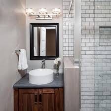 Light-colored walls and white tiled shower walls makes this small, modern  guest bathroom feel larger. A white, round vessel sits below a shiny black  mirror ...
