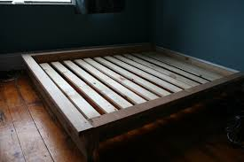 pine wood pallet bed frame with wooden slat placed on varnished white mattress surounding at dark