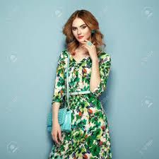 花春夏ドレスで金髪の若い女性ピンクの背景のポーズの女の子夏花の