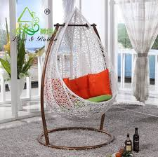 Beautiful Standalone White Hanging Papasan Chair For Indoor Featuring  Orange Pillow And Green Cushion