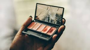 a woman s hand holds a makeup pany with a broken mirror