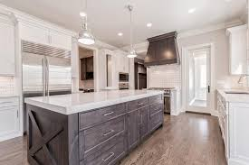 hang over a dark brown kitchen island fitted with stacked drawers as well as x panels placed at each end topped with thick white quartz countertops