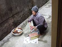 joss paper w burning joss papers in front of her house in hanoi after having offered food to her ancestors