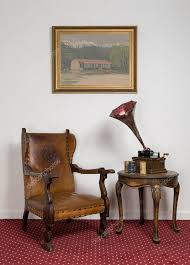 retro leather armchair a 1911 old phonograph with three cylinder records on round coffee table and hanged painting on red carpet photo by