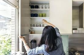 woman reaching into kitchen cabinets how to clean cabinet door hinges