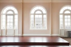 immaculate white painted arched windows frames with cream wall color schemes also great brown veneer wooden floors as modern interior ideas