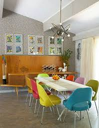 modern dining table with coloured chairs. love the multi-coloured retro dining chairs and sputnik light. modern table with coloured