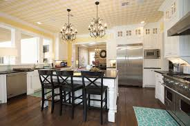 white country kitchen with yellow painted walls chandeliers and black countertops