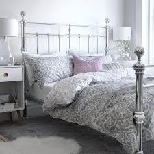 bedroom featuring a metal victoriana style double bed frame with soft grey and pastel pink