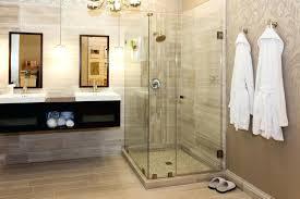 frameless glass shower doors glass shower doors bathrobes patterned wall cream tiles antique chandelier floating vanity