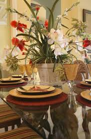 flower arrangements dining room table: a large grouping of orchids and other tropical flowers spill over this glass topped table