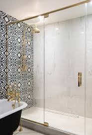 glass and brass shower enclosure filled with marble slabs