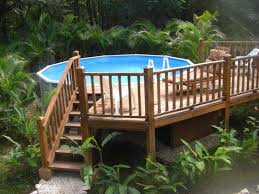 landscaping around above ground pool with deck