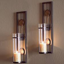 glowing candle on metal wall stand