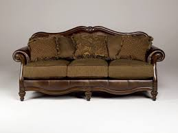 green fabric sofa with three seats and brown wooden arms also brown