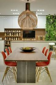 long wooden dining table paired with a set of brightly coloured modern chairs in a contemporary apartment in moscow decorated by
