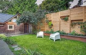 horizontal wood fence with planter box alcoves for hanging plants in backyard