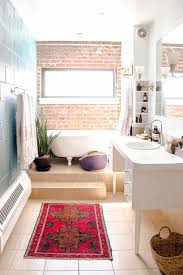 raw brick wall and a bathtub at it to make the bathroom more original
