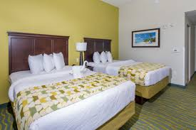 this room has 2 queen beds and space for up to 4 people who will all enjoy the flat screen smart television work area and private balcony with views of