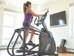 a woman is exercising and doing a hiit elliptical workout