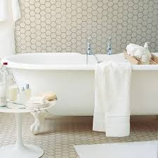 all over tiling white bathroom with hex tile on walls and floor house and