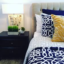 master bedroom with navy blue and white bedding yellow accent throw pillows black bedside