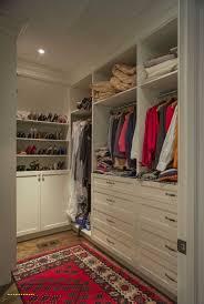 this walk in closet is on the smaller side with white storage drawers and shoe racks