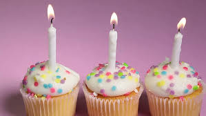 Hd0008three Vanilla Birthday Cupcakes With Lit Candles Being Blown