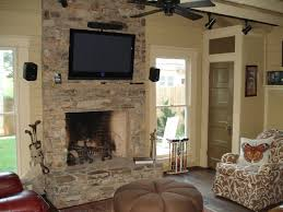 astounding fireplace stone wall decoration ideas for modern living room design interior with tv wall unit also artistic pattern armchair plus round brown