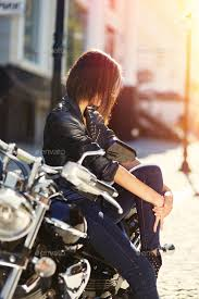 biker girl in a leather jacket on a motorcycle stock photo images