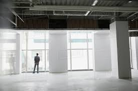 free office space. Businessman At Window Of Empty Office Space Free F