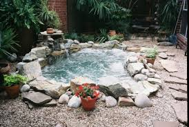 beautiful in ground natural looking stone hot tub surrounded by pebbles