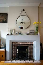 decorative mirrors for above fireplace. a round mirror hangs from leather strap above modern fireplace mantel. | lonny decorative mirrors for