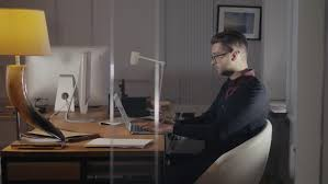 home office multitasking. wonderful office multitasking handsome young man wearing glasses and working withlaptop  while sitting in modern office throughout home office multitasking