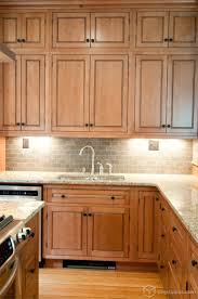 hard maple wood colonial raised door light kitchen cabinets marble countertops lighting flooring sink faucet island
